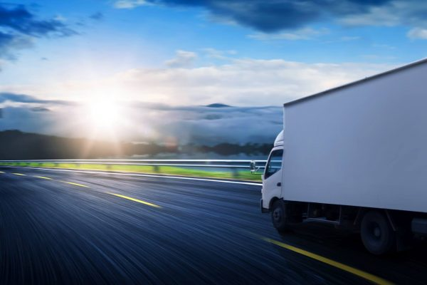 Truck traveling on road at sunrise - speed and delivery concept.