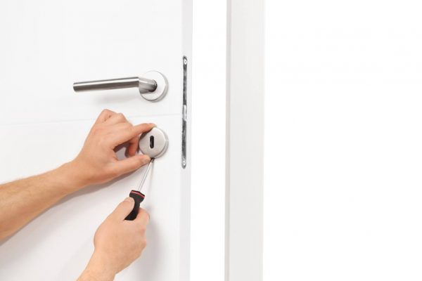 Studio shot of a young male locksmith installing a lock on a white door with a screwdriver isolated on white background
